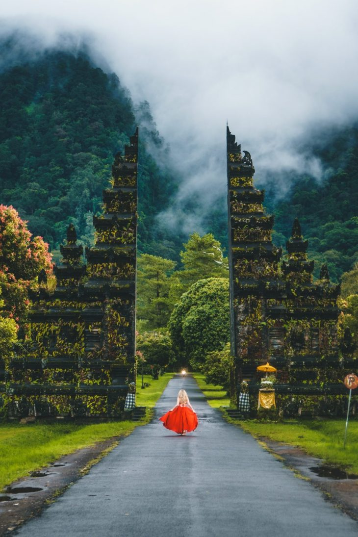 Woman wearing red dress running toward gate overlooking foggy mountain during daytime